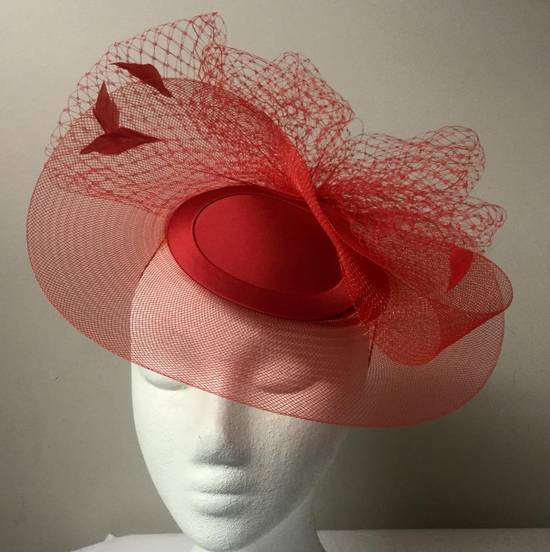 Red cocktail hat with veiling and feathers