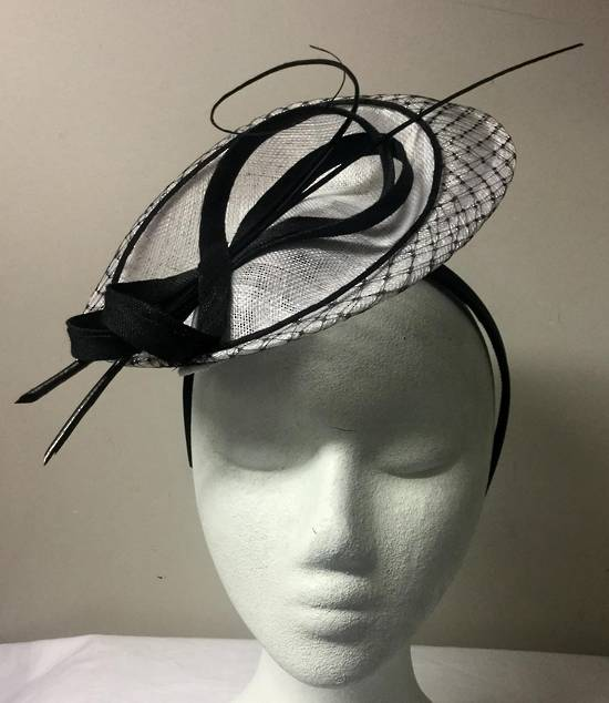 White and black small hat on headband with black loops and sticks