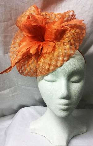 Orange check fascinator with feather flowers on a headband